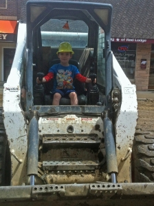 My grandson posing in a piece of construction equipment outside of our store.